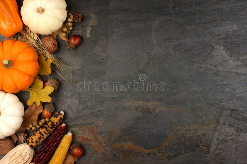 Autumn harvest side border over a slate background stock image