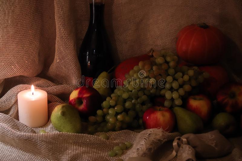 Autumn harvest still life. Apples, pears, grapes and pumpkin on sackcloth backgound with bottle of wine and candle light. Autumn harvest still life. Group of royalty free stock photos
