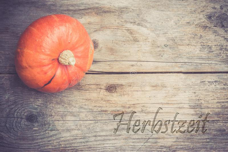 Autumn and harvesting: Pumpkin is lying on a rustic, wooden table.& x22;Herbstzeit. Orange pumpkin is lying on a rustic wooden table. & x22;Herbstzeit halloween stock photos