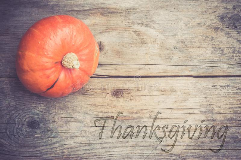 Autumn and harvesting: Pumpkin is lying on a rustic, wooden table.Thanksgiving. Orange pumpkin is lying on a rustic wooden table. & x22;Thanksgiving halloween royalty free stock images