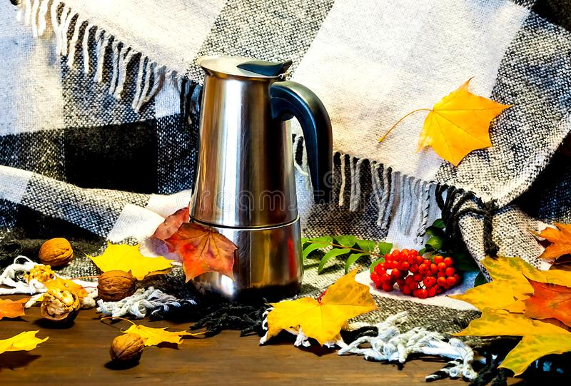 Autumn home decor. Metal coffee pot amid bright yellow leaves on Checkered Plaid. Hygge Style, concept of comfort and coziness.n. Autumn home decor. Metal coffee stock images