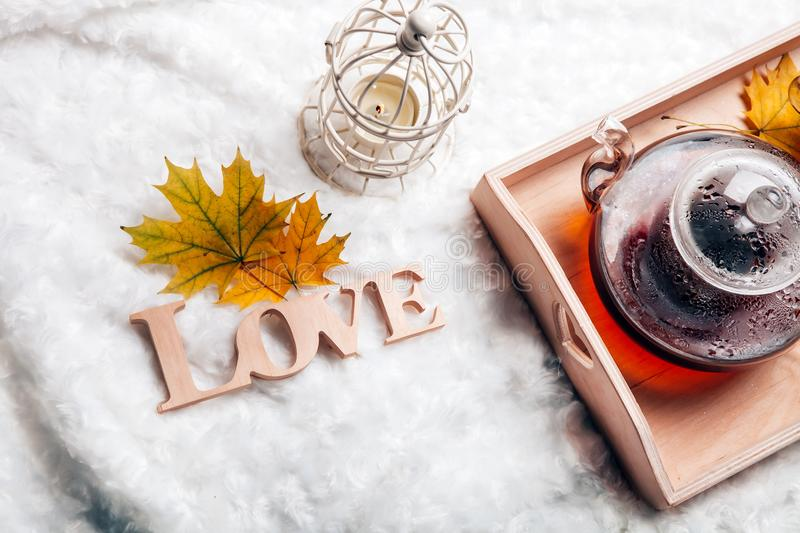 Autumn home scene, Scandinavian style. A warm knitted sweater, candles, a cup of warm tea and other decor on a tray in bed. Lazy c stock photography