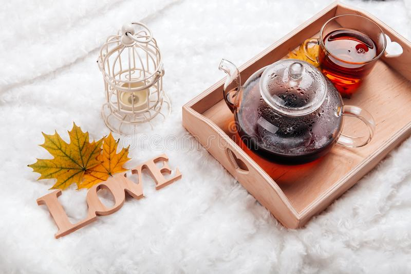 Autumn home scene, Scandinavian style. A warm knitted sweater, candles, a cup of warm tea and other decor on a tray in bed. royalty free stock photo