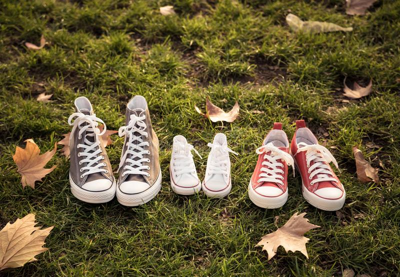 Autumn image of family shoes sneakers gumshoes on grass in sunset light in outdoors family lifestyle stock photos