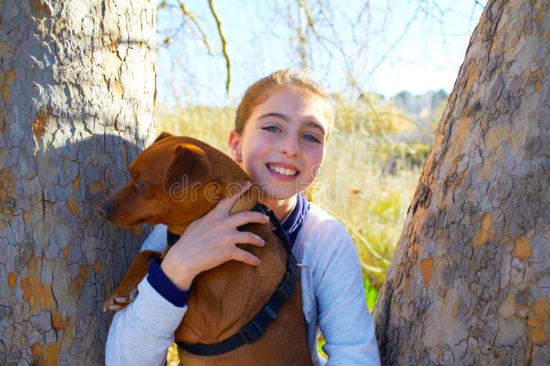 Autumn kid girl with pet dog relaxed in fall forest stock images