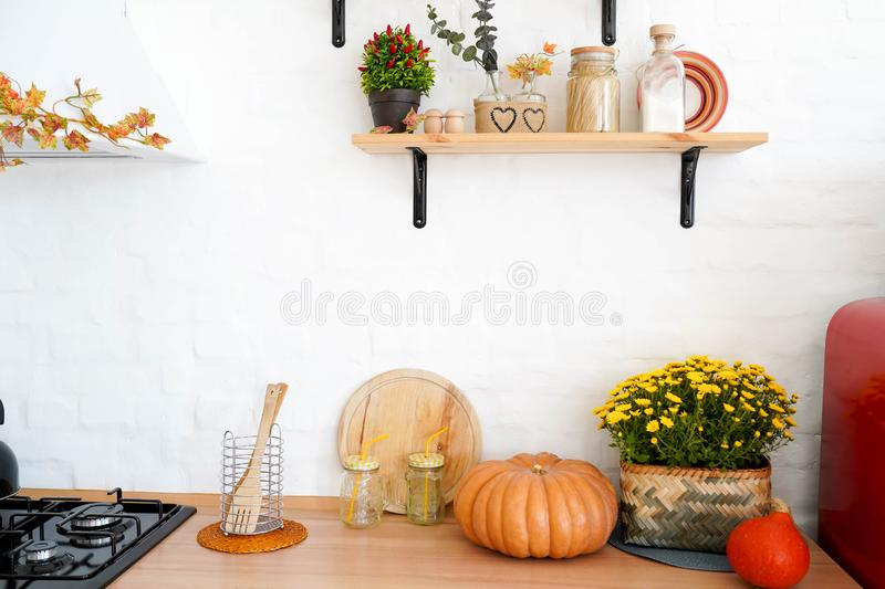 Autumn kitchen interior with shelfs, yellow flowers and pumpkin.  royalty free stock photography