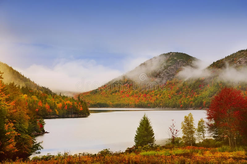 Autumn lake in the mountains. Lake in the mountains, colors around autumn trees. Acadia National Park. Maine. USA. Cloudy gloomy weather, fog and clouds over the royalty free stock photography