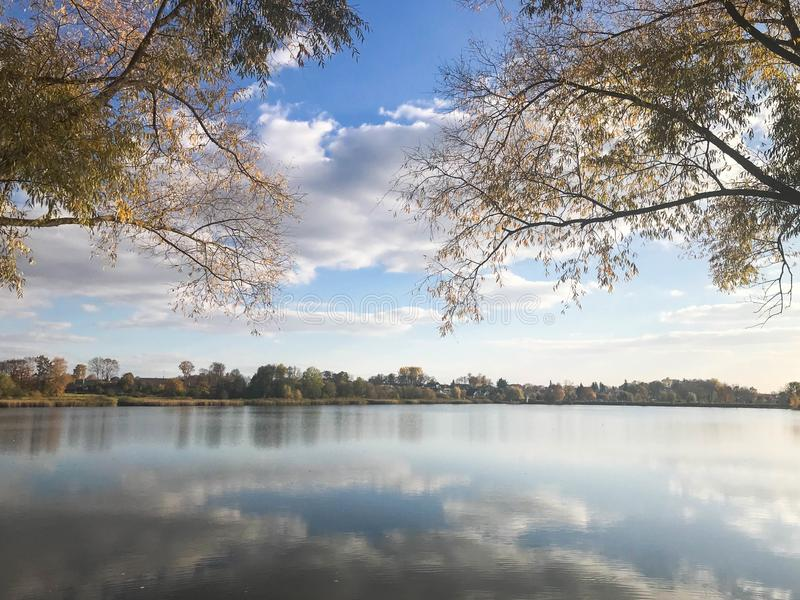 Autumn landscape beautiful with trees and yellow leaves on the lake against the blue sky on a sunny day royalty free stock photography