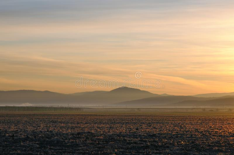 Autumn landscape with cleaned agricultural field during spectacular gold sunrise above smooth hills. In Khakassia, Russia stock images