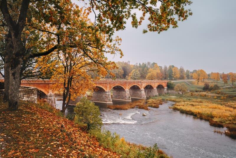 Autumn Landscape De Oude Baksteenbrug over de Venta-rivier binnen royalty-vrije stock fotografie