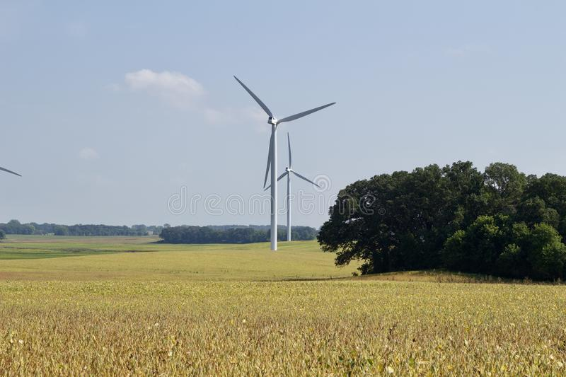 Autumn landscape with giant wind power turbines in a crop field royalty free stock photography