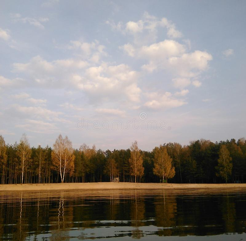 Autumn landscape on the lake. The blue sky with white clouds against the background of a languid smooth surface of the quiet lake in the fall stock photo