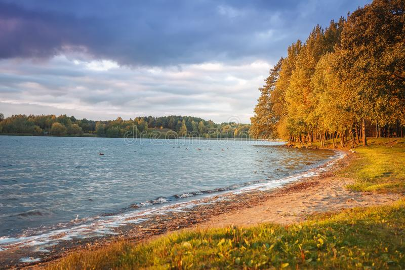 Autumn landscape of lake and colorful trees on shore in the evening. Yellow and red leaves on tree in october. Scenery of fall. Colored nature in sunlight stock image