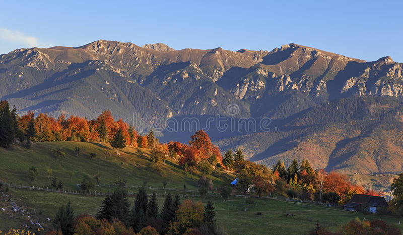 Autumn landscape in mountains. Deciduous forest in hills. Stack dry hay in meadow. Beautiful sunset. royalty free stock images