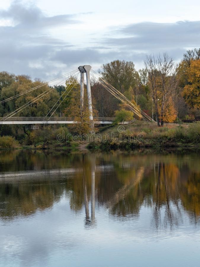 Autumn landscape with river, bridge and beautiful colorful trees, river Gauja, Valmiera, Latvia. Beautiful autumn landscape with river, bridge and beautiful royalty free stock image