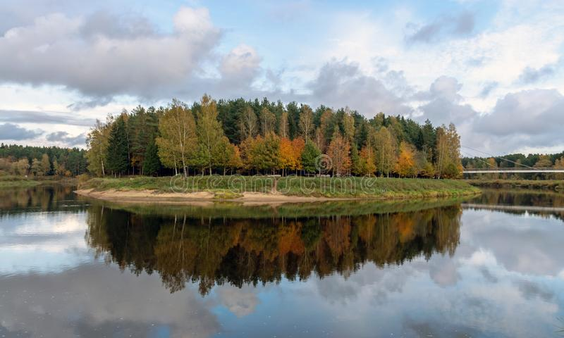 Autumn landscape with river, bridge and beautiful colorful trees, river Gauja, Valmiera, Latvia. Beautiful autumn landscape with river, bridge and beautiful stock photography
