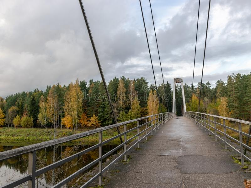 Autumn landscape with river, bridge and beautiful colorful trees, river Gauja, Valmiera, Latvia. Beautiful autumn landscape with river, bridge and beautiful royalty free stock photography