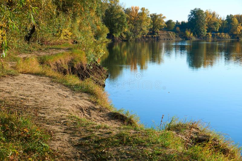 Autumn landscape of river and bright trees and bushes stock photography