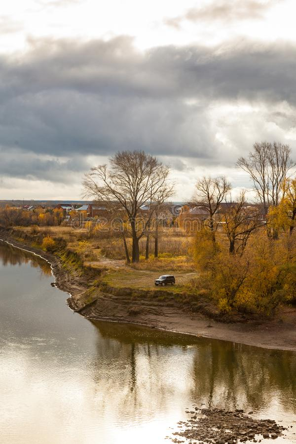 Autumn landscape with river and autumn trees. Autumn landscape with river and autumn forest. On the shore is a car stock photos