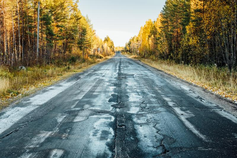 Autumn landscape with road by damaged asphalt, trees and sky stock photos