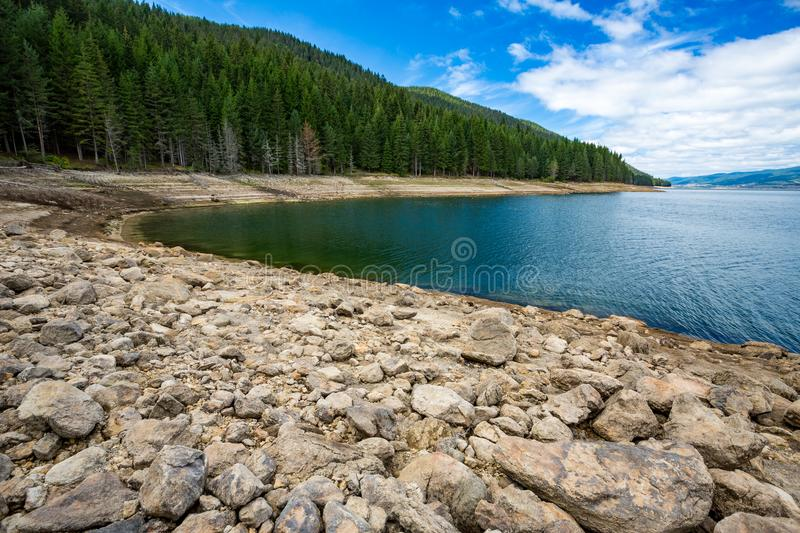 Autumn landscape rocky shore at Dospat, Bulgaria. Autumn landscape at lake Dospat, Bulgaria, looking West. Overcast sky. Rocky shore and calm blue waters. Pine royalty free stock photography