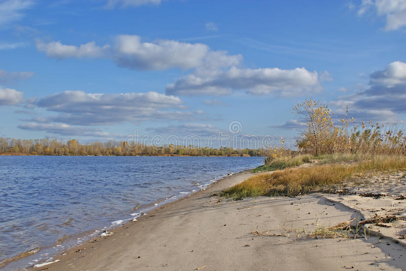 Autumn landscape on the sandy shore of the great river. Scenic clouds on the blue sky. Sunny day in October royalty free stock photo
