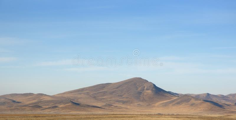 Autumn landscape with smooth hills covered with dry yellow grass under blue sky. In Khakassia, Russia royalty free stock photography
