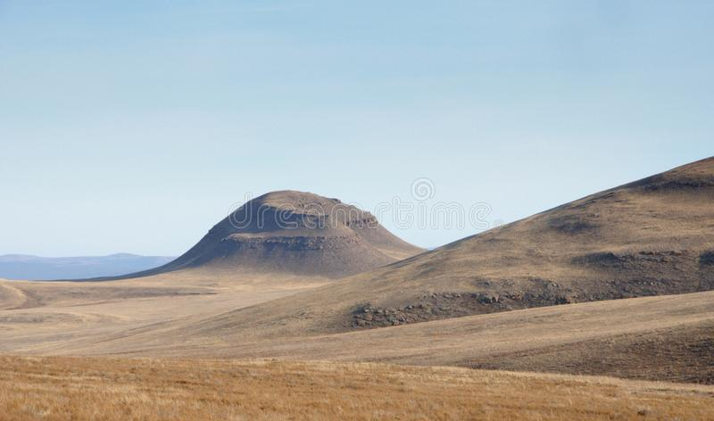 Autumn landscape with smooth hills covered with dry yellow grass under blue sky. In Khakassia, Russia stock photography