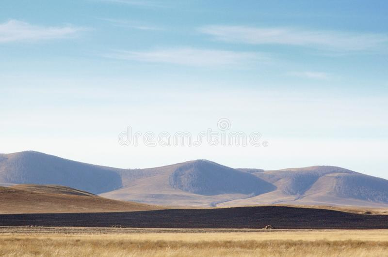 Autumn landscape with smooth hills covered with dry yellow grass under blue sky. In Khakassia, Russia royalty free stock photo