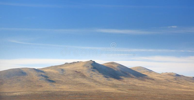 Autumn landscape with a smooth hills covered with a yellow dry grass under dark blue sky. In Khakassia, Russia stock photography