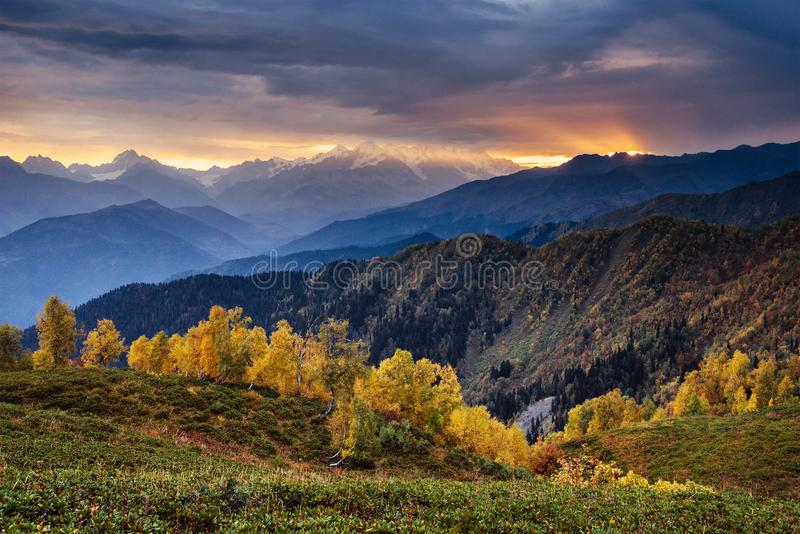 Autumn landscape and snowy mountain peaks. Birch forest in sunlight. Main Caucasian Ridge. Mountain View from Mount royalty free stock photography
