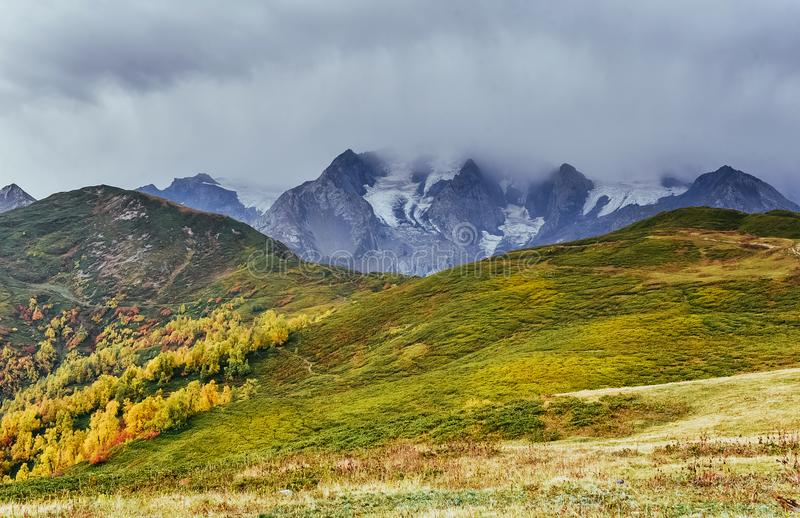 Autumn landscape and snowy mountain peaks. Birch forest in sunlight. Main Caucasian Ridge. Mountain View from Mount stock photo