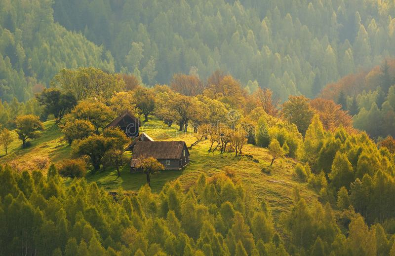 Autumn landscape at sunrise in Transylvania, Romania - traditional house on a hill in the forest - Morning Mist royalty free stock image