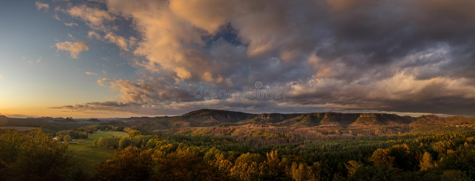 Autumn landscape at sunset - mountains, forests and beautiful clouds illuminated by the setting sun stock photography