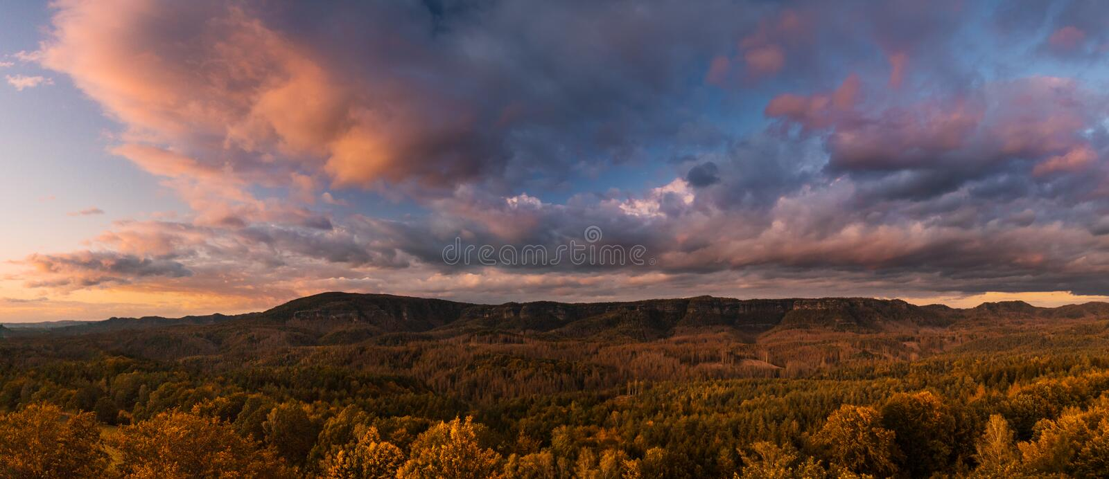 Autumn landscape at sunset - mountains, forests and beautiful clouds illuminated by the setting sun royalty free stock image
