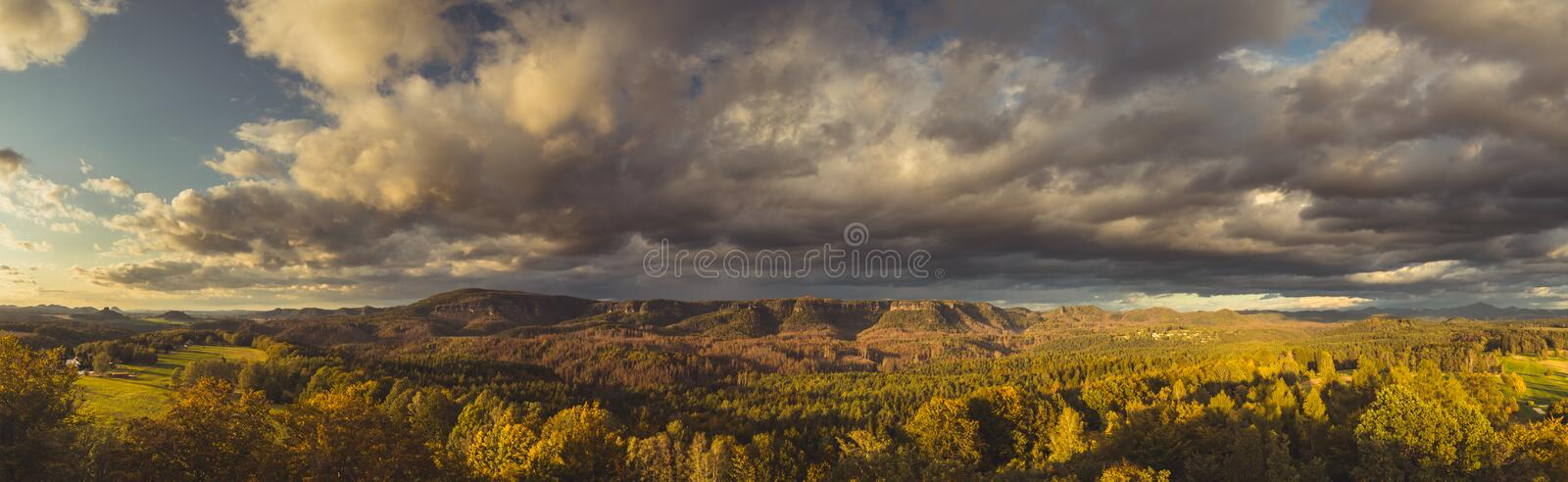 Autumn landscape at sunset - mountains, forests and beautiful clouds illuminated by the setting sun stock photo