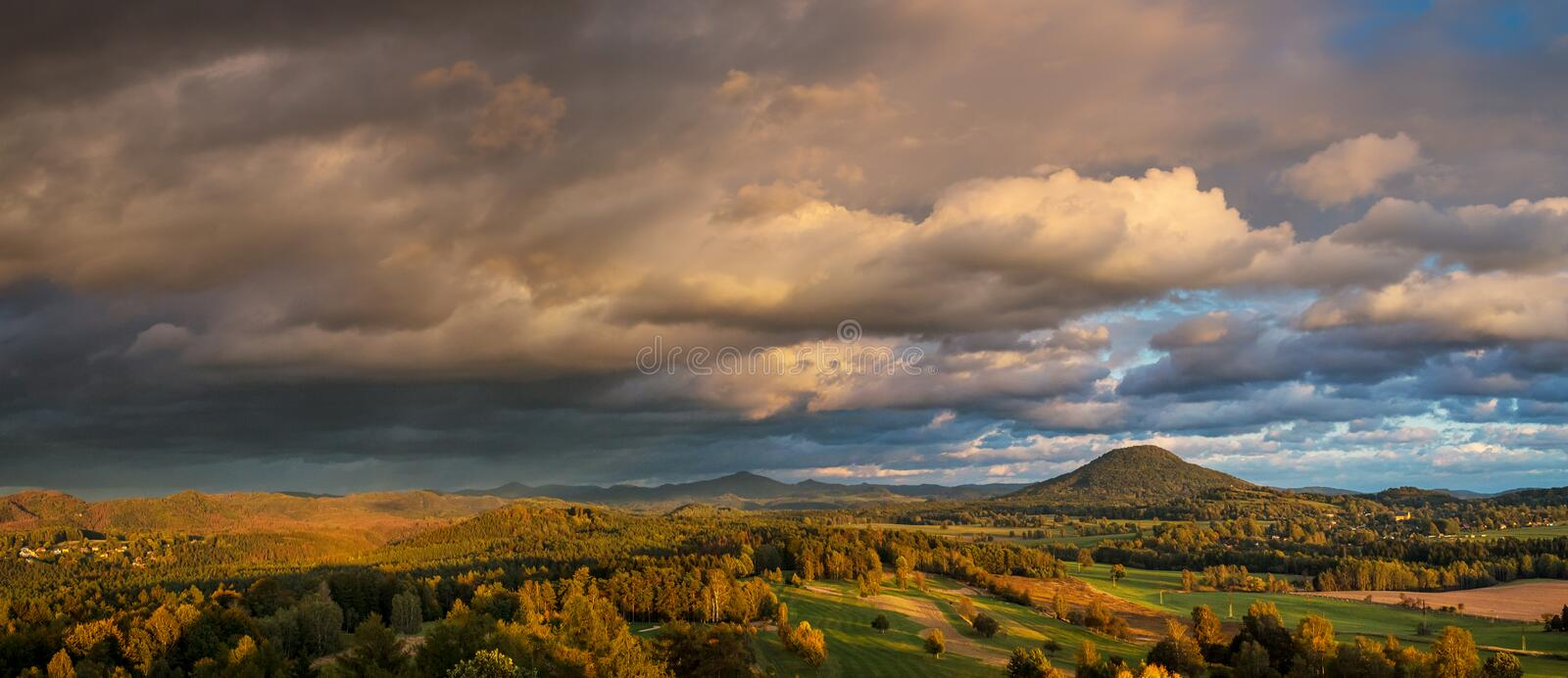 Autumn landscape at sunset - mountains, forests and beautiful clouds illuminated by the setting sun stock photos