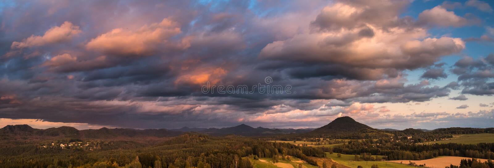 Autumn landscape at sunset - mountains, forests and dramatic clouds illuminated by the setting sun stock images