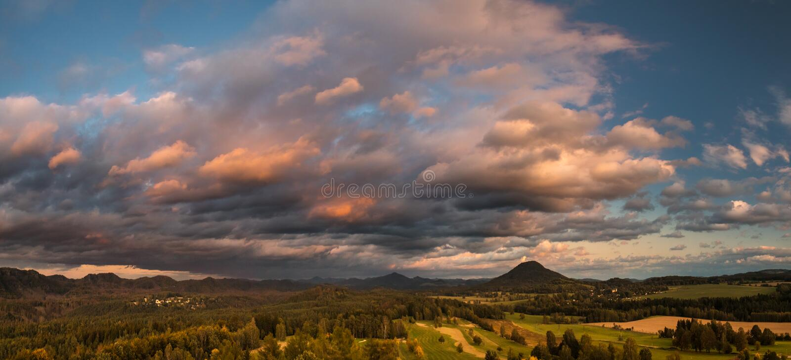 Autumn landscape at sunset - mountains, forests and dramatic clouds illuminated by the setting sun royalty free stock image