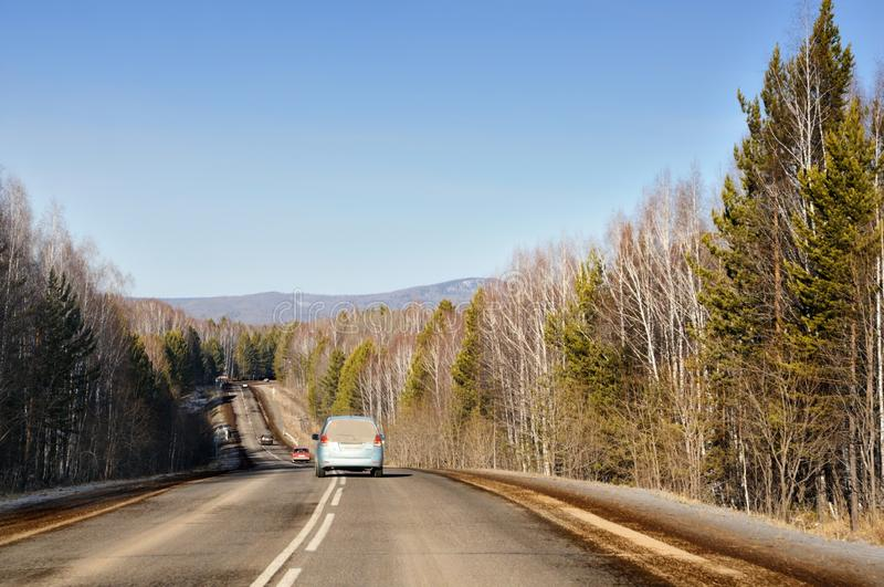 Autumn landscape with tarmac road on the smooth hills covered with taiga forest under blue sky. In Siberia, Russia stock images