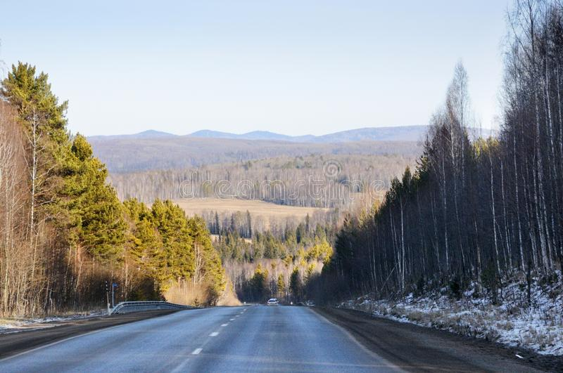 Autumn landscape with tarmac road on the smooth hills covered with taiga forest under blue sky. In Siberia, Russia stock photos