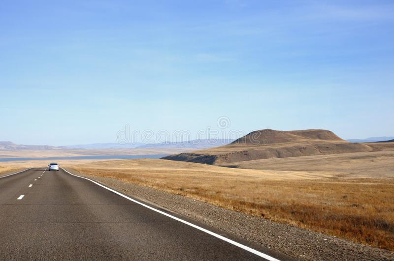 Autumn landscape with tarmac road to horizon between smooth hills covered with dry yellow grass under blue sky. In Khakassia, Russia royalty free stock image