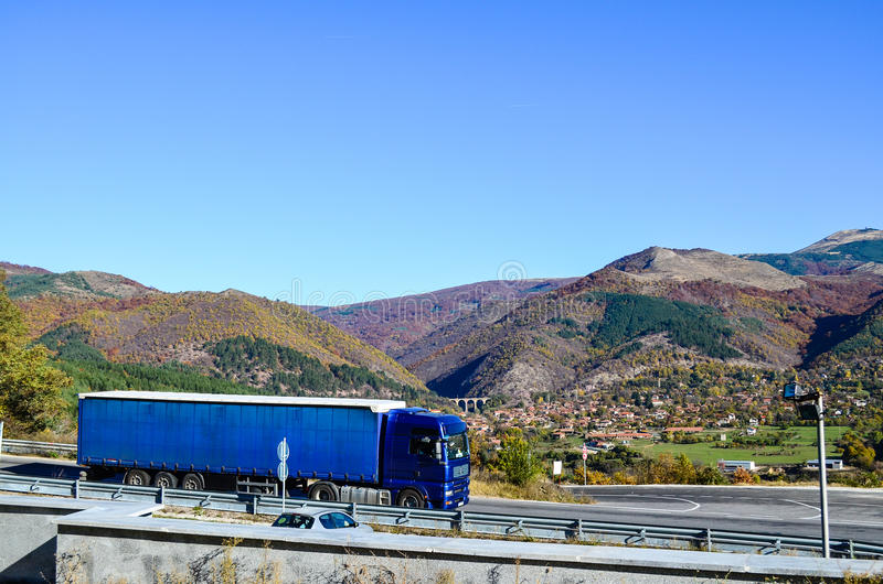 Autumn landscape. A truck on a road and a little village from above in the autumn stock photography
