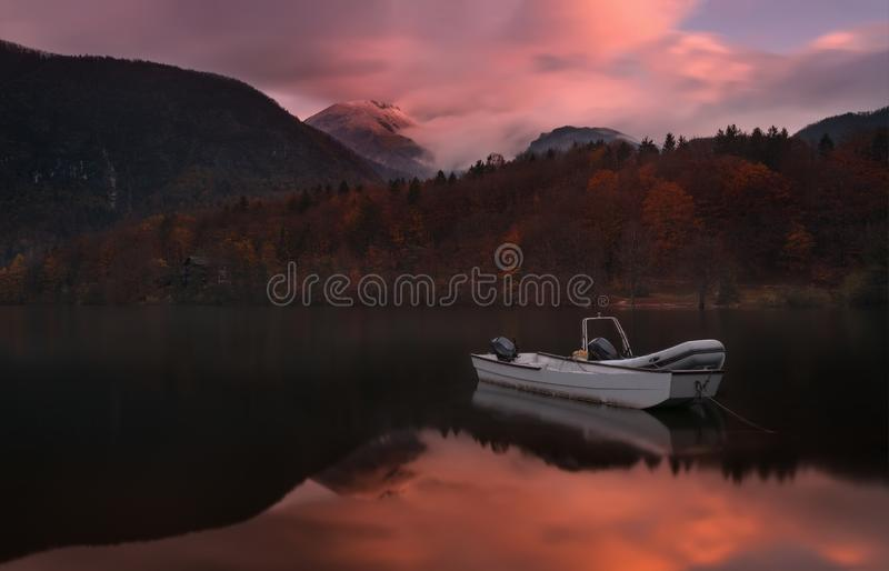 Autumn Landscape  With Two White Boats Of The Rescue Service Against The Backdrop Of The Reflection Of  Triglav Mountains,  Fiery royalty free stock photography