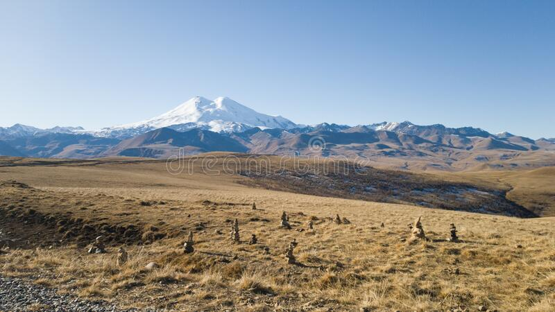 Autumn landscape. View of the dry yellow field and the beautiful mount Elbrus in the Caucasus. Pyramids of stones stock photo