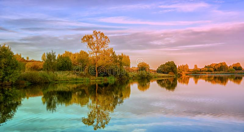 Autumn landscape with water, colorful trees stock photography
