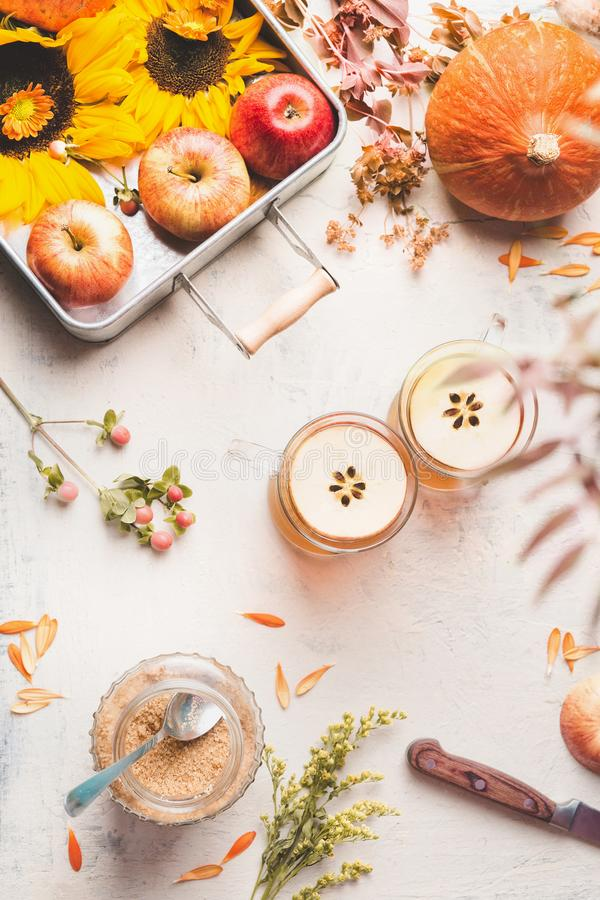 Autumn layout. Glass mugs with apple hot cider or apple mulled wine with apple slices on white desktop with sunflowers, pumpkin stock images
