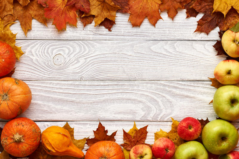 Autumn Leaves Apples And Pumpkins Over Wooden Background