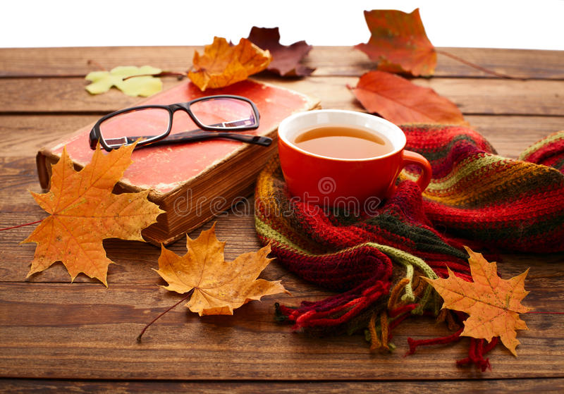 Autumn leaves, book and cup of tea on wooden table royalty free stock image