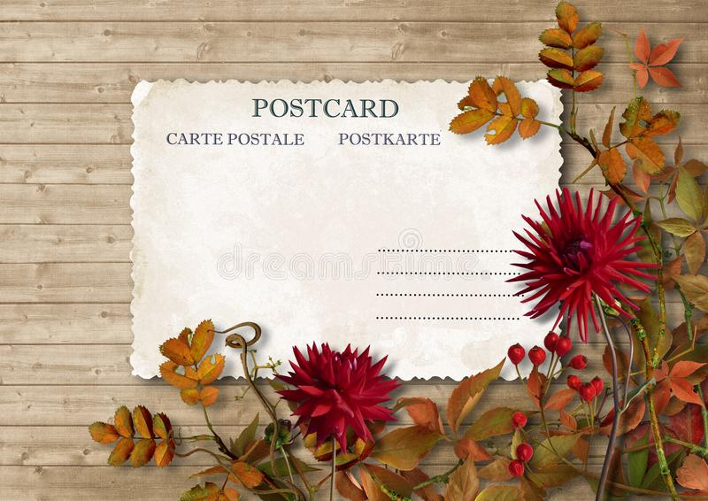 Autumn leaves and dahlias with postcard on vintage background royalty free stock image